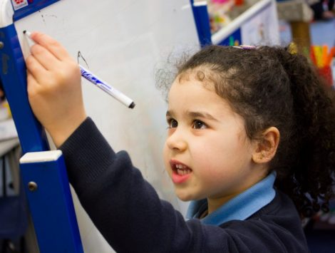 Girl pupil writing on whiteboard in classroom at The Lea Primary School and Nursery
