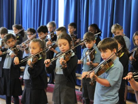 The Lea Primary School and Nursery pupils playing the violin in the hall