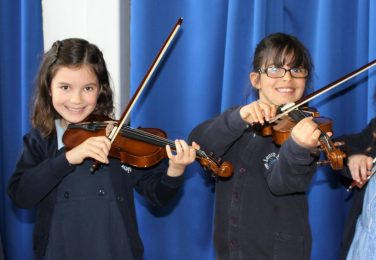 The Lea Primary School and Nursery happy girls playing the violin in the hall