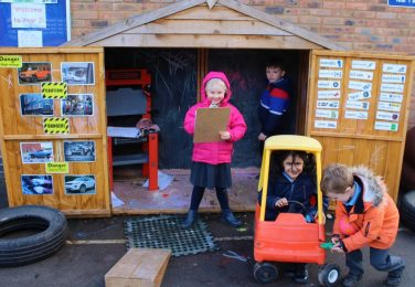 Reception pupils playing in the car workshop at The Lea Primary School and Nursery