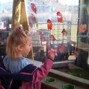Reception pupil playing with painting wall at The Lea Primary School