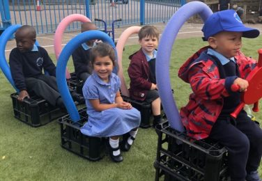 Nursery and Reception pupils sitting in an imaginary school bus at The Lea Primary School and Nursery