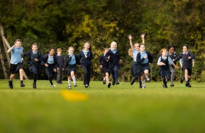 Happy pupils running across the field at The Lea Primary School and Nursery