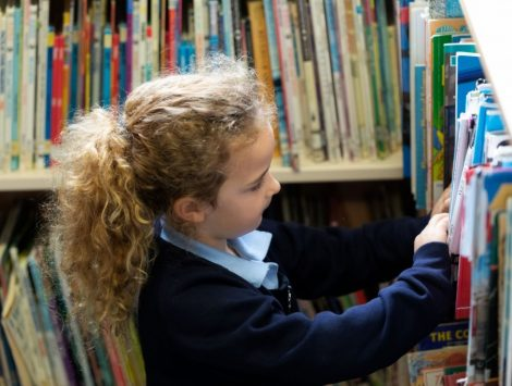 Girl pupil looking through books in the school library at The Lea Primary School and Nursery