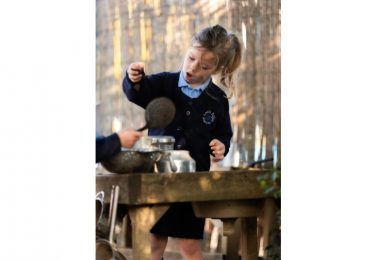 Happy Reception pupil playing in mud kitchen at The Lea Primary School