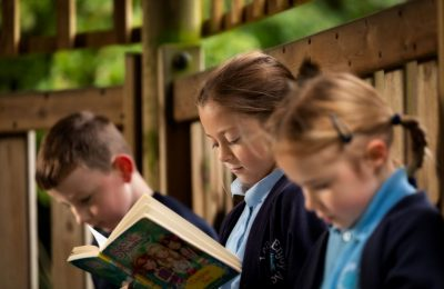 Pupils reading in the outdoor classroom at The Lea Primary School and Nursery
